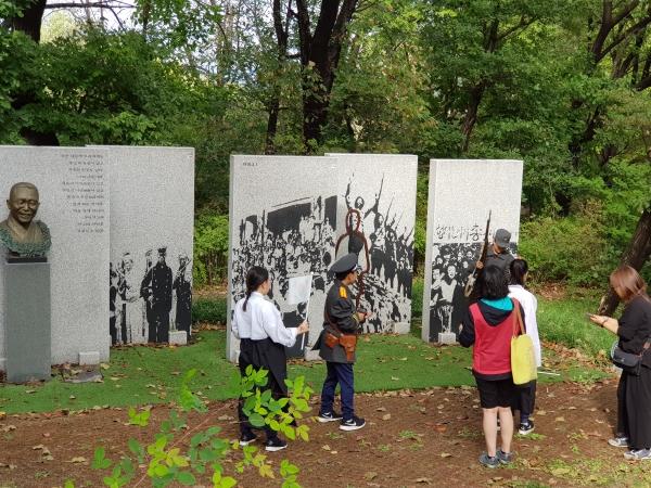 2.지난해 9월 역사 탐방 여행 때 근현대사기념관 앞에 있는 독립민주 기념비에서 의상 체험하는 학생들.